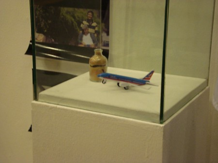 Iconic items from Transit at the Cinemalayà 2013 exhibit, showing a toy plane and a vial of sand