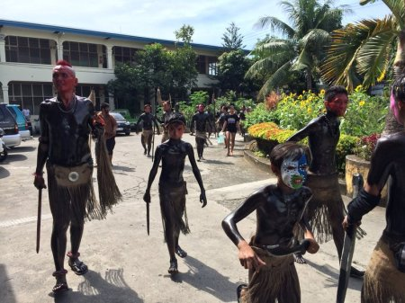 Ati-atihan dancers, in full black paint costume, arriving at the Asilo de la Milagrosa