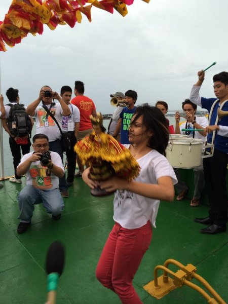 Young lady dancing the sinulog on a ferry's foredeck