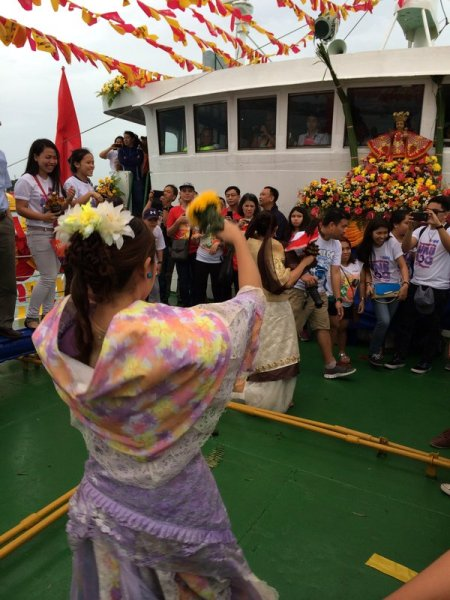 Sinulog dancers in Filipiniana costume on a ship's foredeck