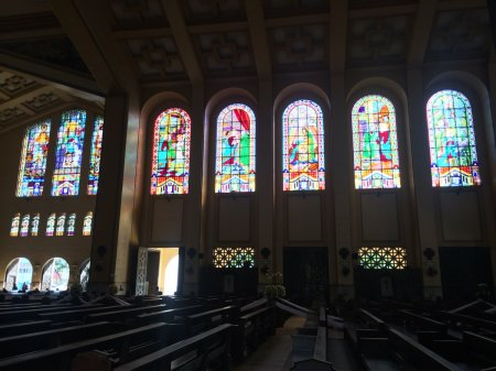 The eastern stained glass windows of Santo Domingo church, glowing and viewed from the inside