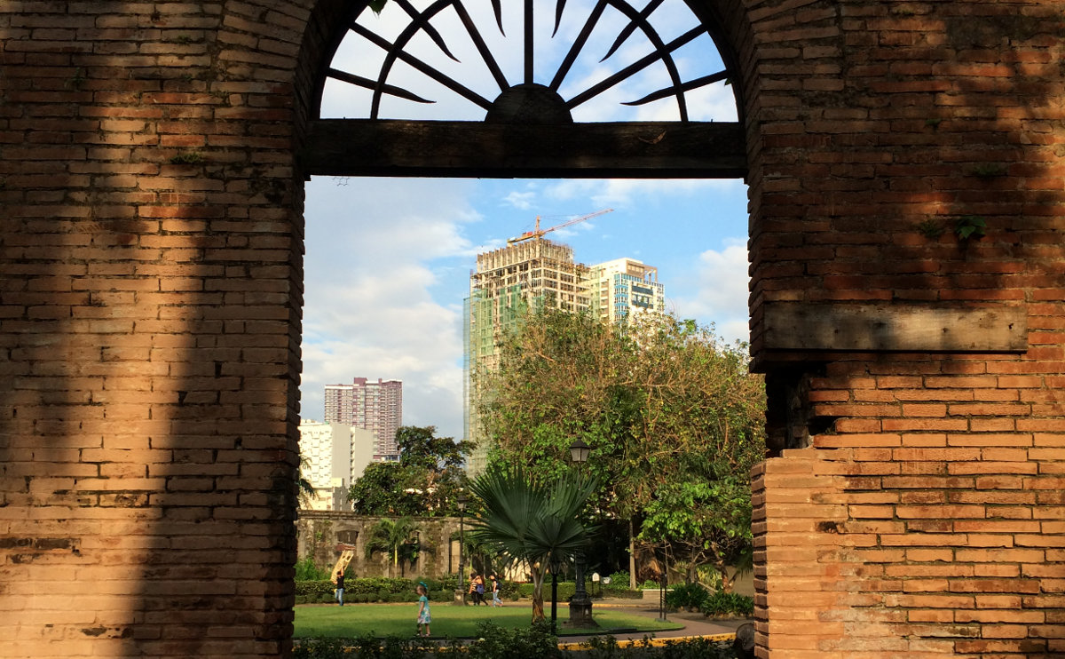 A tall, modern building under construction, viewed through an old doorway in Manila's Fort Santiago.