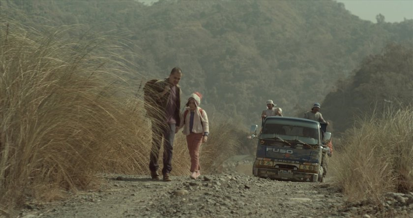Image from Honor Thy Father (2015) of a man and a child walking on a mountain dust road.