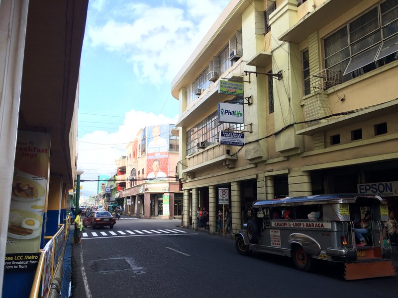 A street in Legazpi Port District with American colonial-style buildings.