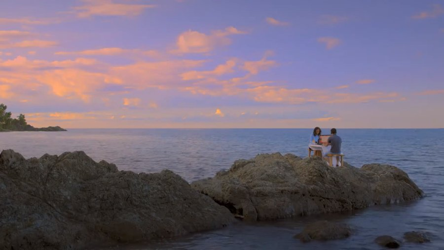 Surreal scene from Water Lemon (2015), showing two characters chatting through computers on a coastal rock under a sunset.