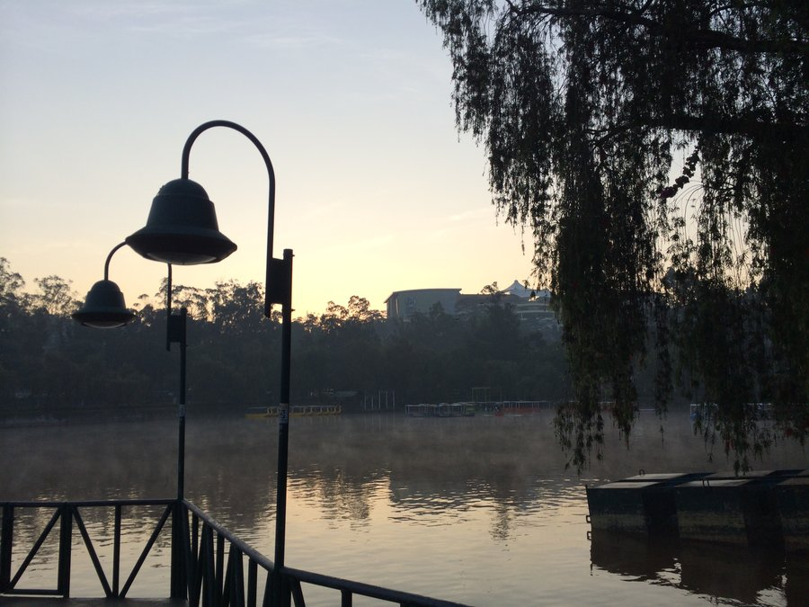Sunrise view of the lake at Burnham Park in Baguio, with mist floating over the water's surface.