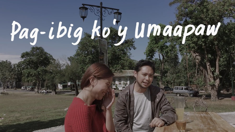"A man and a woman share a light moment in the Ang Bandang Shirley music video for Umaapaw, under handwritten lyrics, ""Pag-ibig ko'y umaapaw."""