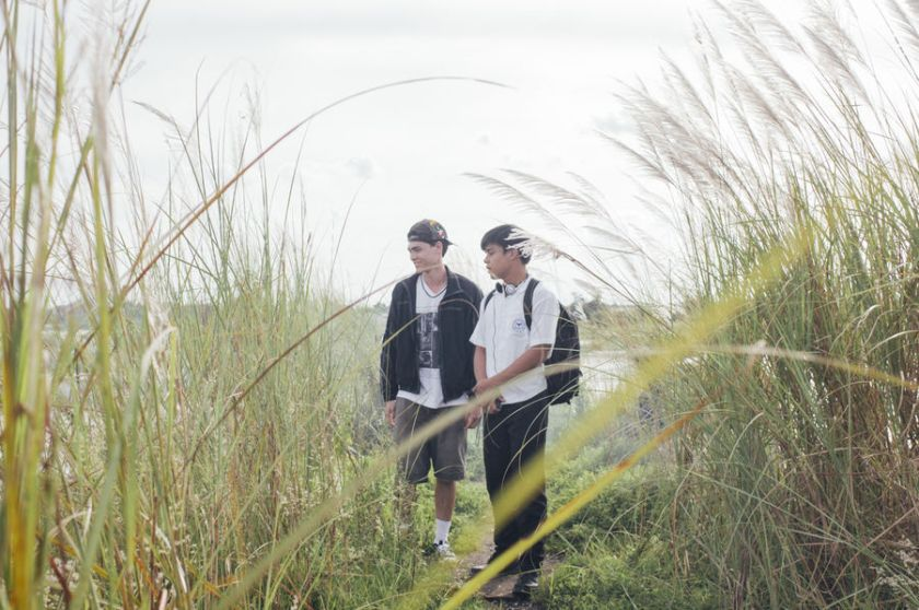 Magnus (Ethan Salvador) and Felix (Khalil Ramos) walk among tall grass at the Megadike, in 2 Cool 2 Be 4gotten (2016).