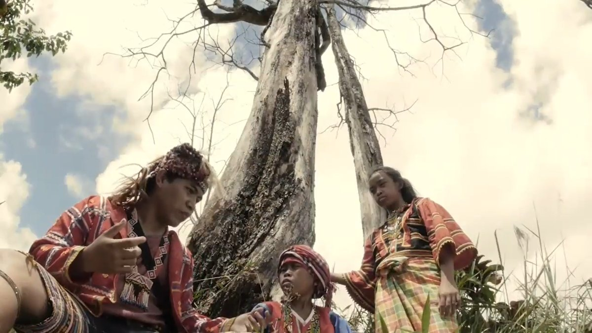 Scene from 'Tu Pug Imatuy': a lumad father telling stories to his children under a tree.
