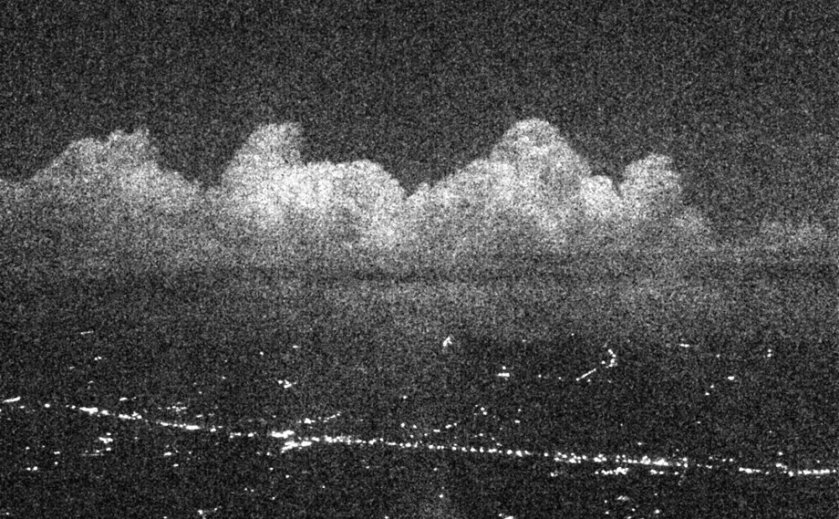 Grainy image of clouds, taken from an airborne plane, illuminated by the moon.