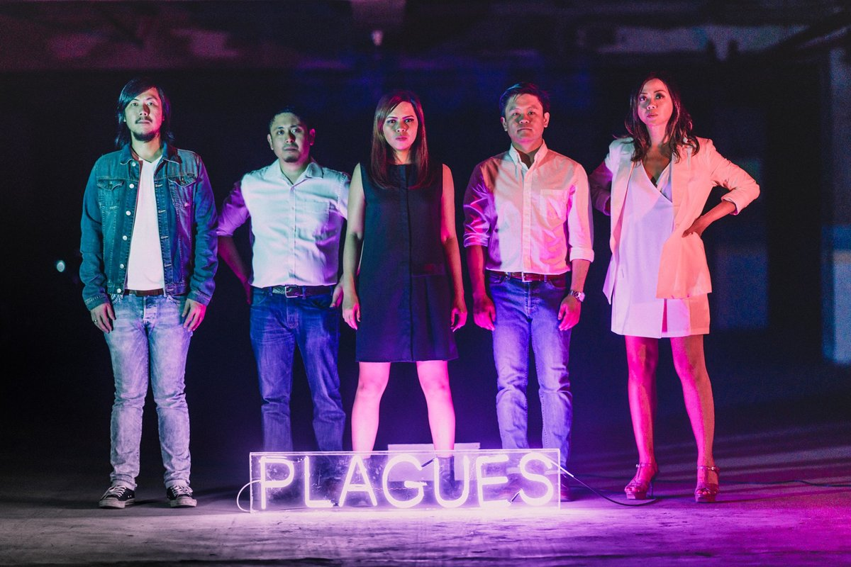 The members of Taken by Cars, standing behind a neon sign and illuminated by colorful lighting.