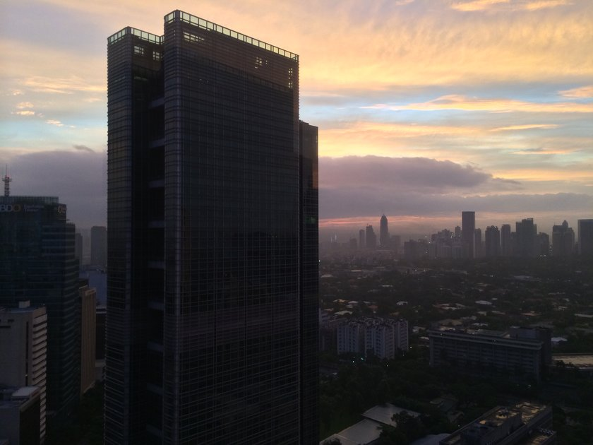 Colorful skyline view of Makati City at dawn.