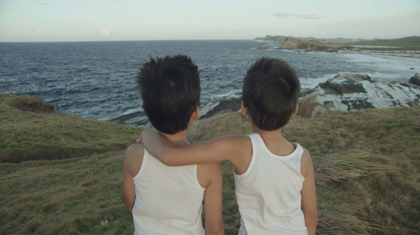 Twin brothers looking over the sea from a grassy vantage point, in 'Hilom'.