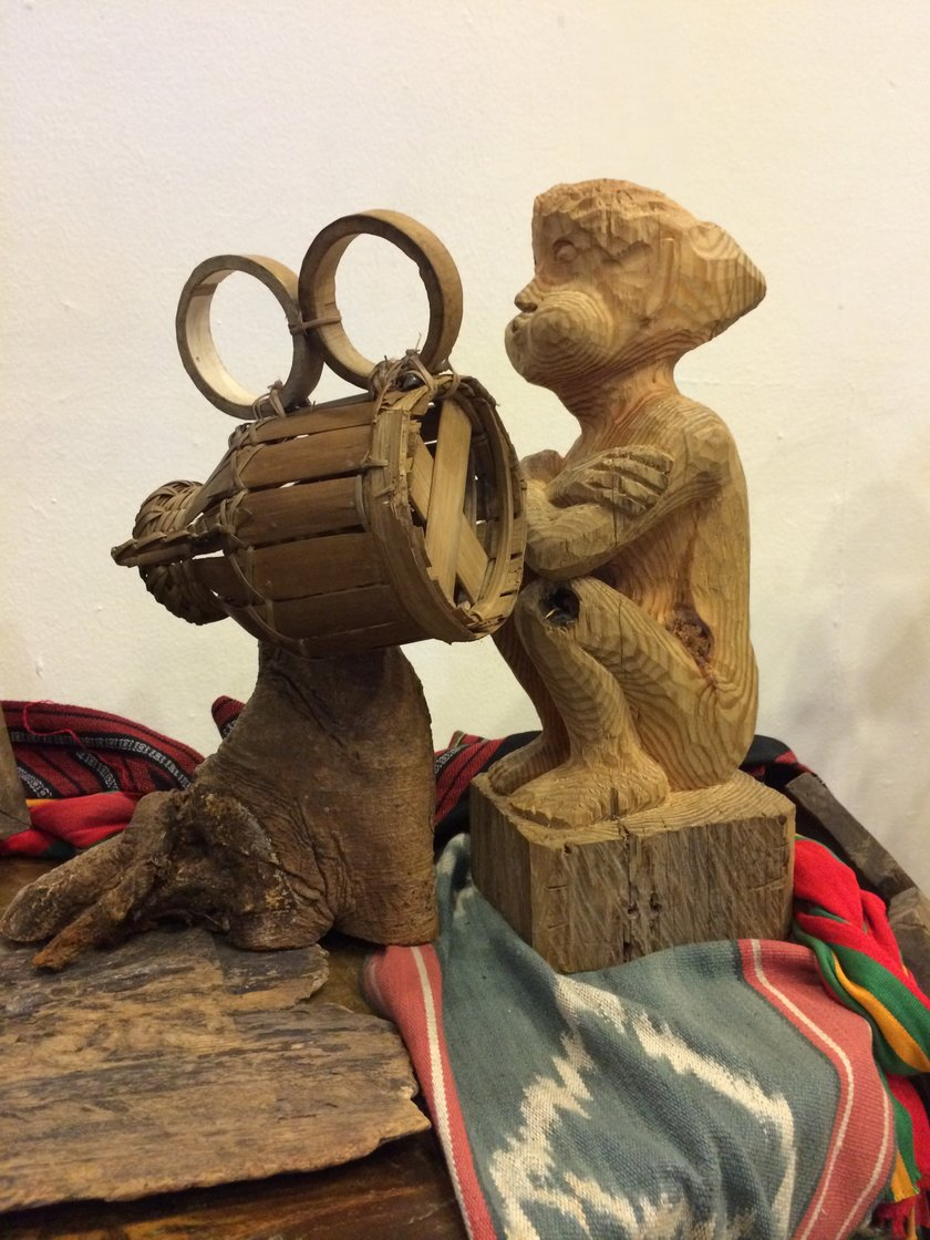 Wooden sculptures of a sitting figure (a Cordilleran bulol) and a movie camera, from an exhibit by Kidlat Tahimik.