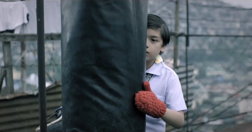 Noel Comia, Jr. as the young Kiko in 'Kiko Boksingero', hiding behind a punching bag.