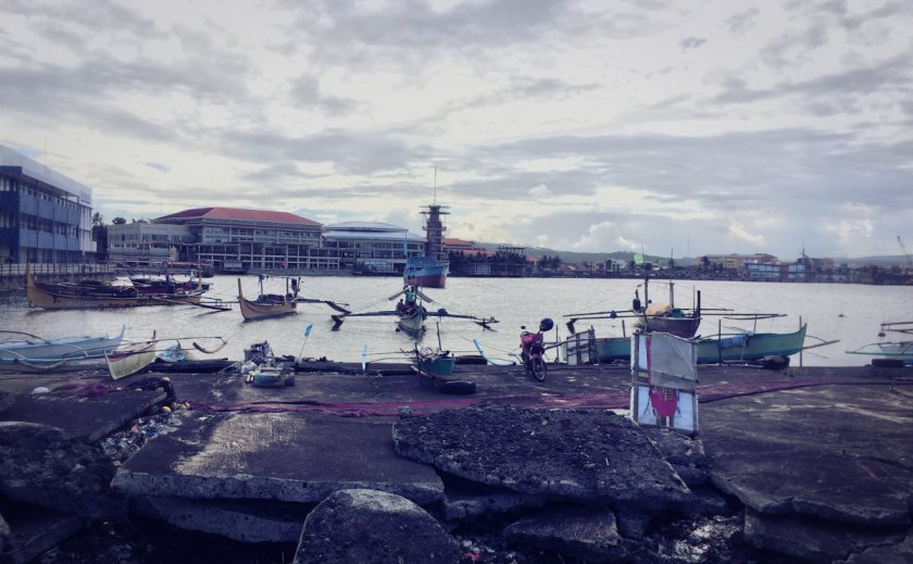 The port area in Legazpi City, with boats, a ship, and the Embarcadero mall.