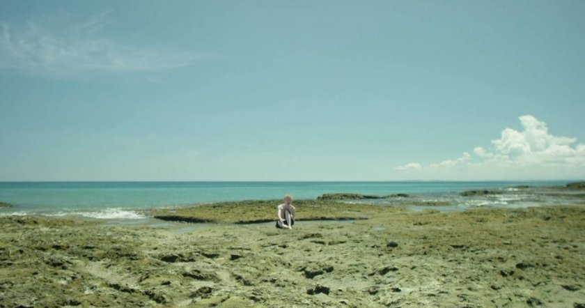 A boy afflicted with albinism is sitting on the beach under the sun, in 'Medusae' (2017).