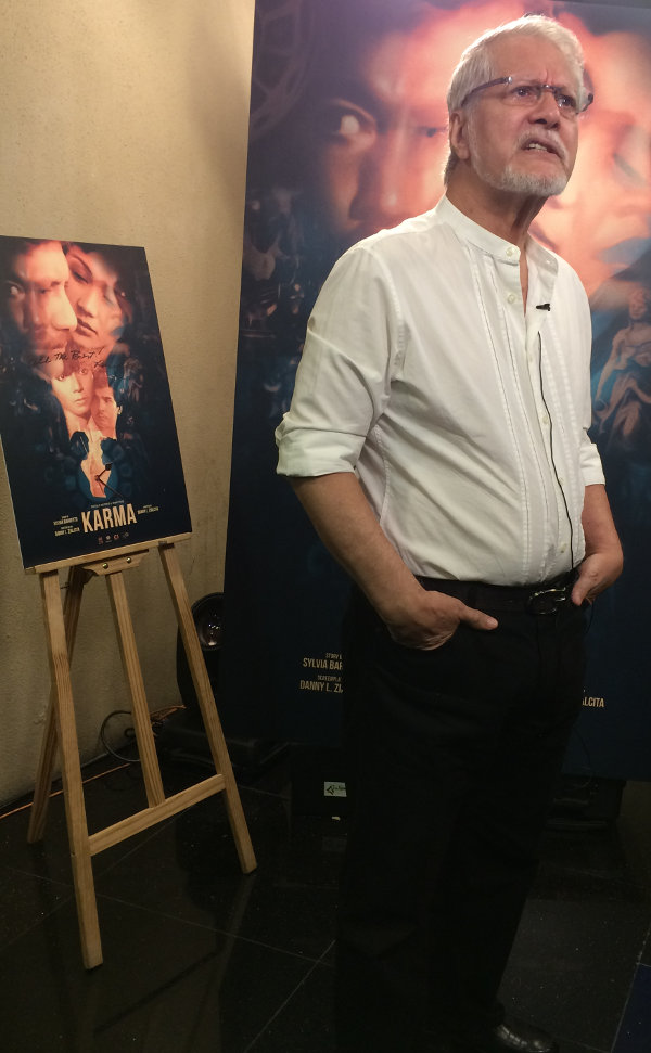 Ronaldo Valdez standing in front of movie posters at the premiere for the digitally restored 'Karma'.