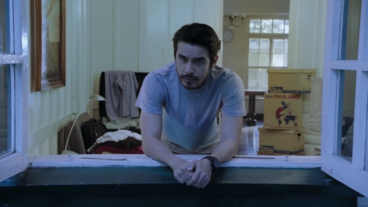 Atom Araullo looking out from a window, and straight at the camera, as Jake in 'Citizen Jake' (2018).