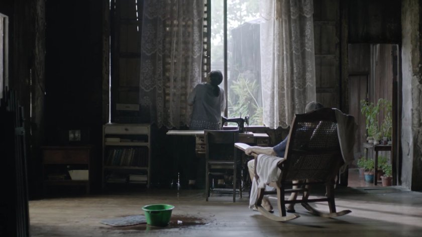 Perla Bautista as Terê opening the window while Dante Rivero as Bene watches from a rocking chair in 'Kung Paano Hinihintay ang Dapithapon' (2018).