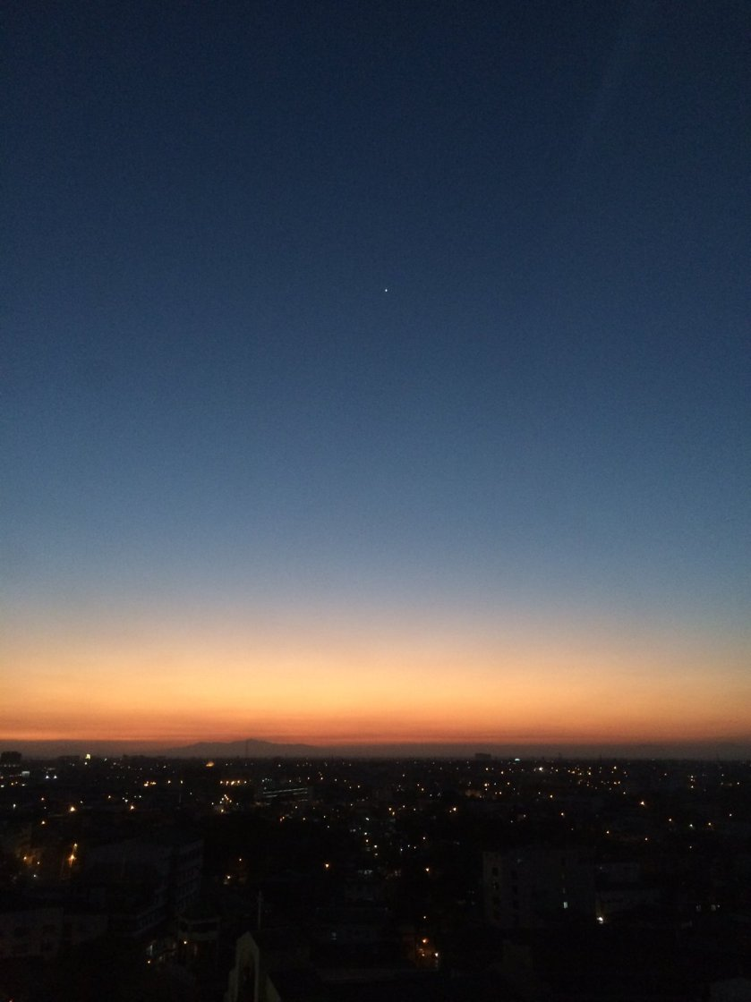 Sunset over Quezon City showing the orange-to-blue color gradient of the sky.