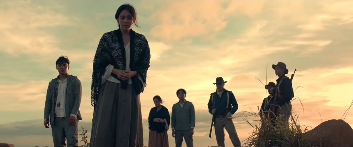 Carlo Aquino as Colonel Vicente Enríquez, Empress Schuck as Felicidad Aguinaldo, and other figures looking sadly over something on the ground at twilight, in 'Goyo: Ang Batang Heneral'.