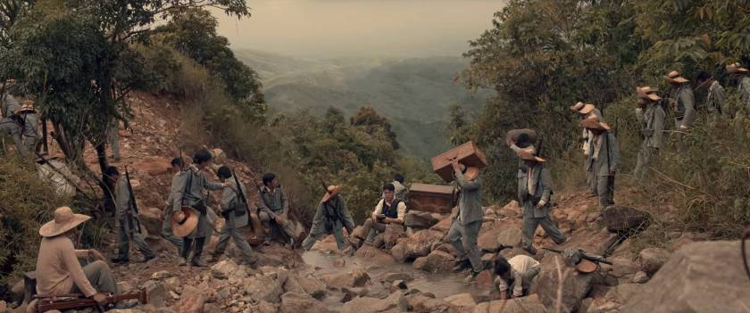 Filipino revolutionary soldiers crossing a stream, carrying supplies, in difficult mountainous terrain, in 'Goyo: Ang Batang Heneral'.