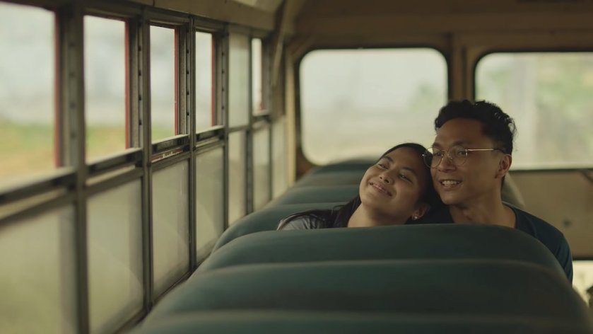 Anna Luna and Nicco Manalo as Anna and Sam happily sitting in an abandoned bus, in 'Tayo sa Huling Buwan ng Taon' (2019).