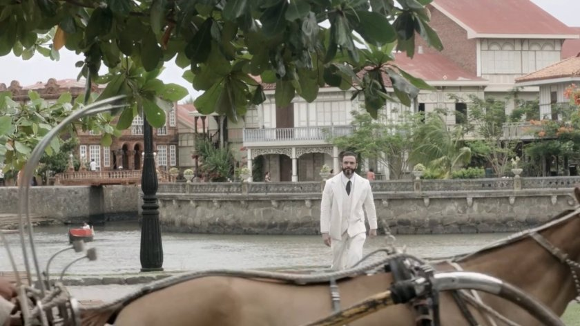 Billy Ray Gallion as Alex Frieder, walking in a white suit beside the river in pre-war Manila, in 'Quezon's Game' (2018).