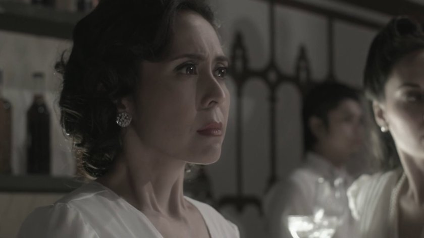 Rachel Alejandro as Aurora Quezon, wearing a white dress and looking worried as she observes a party, in 'Quezon's Game' (2018).