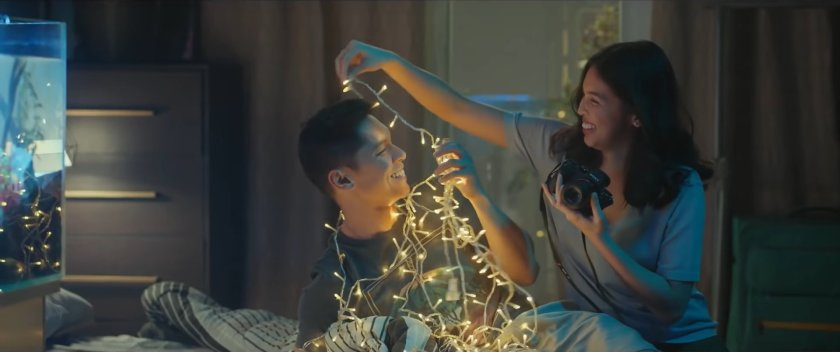 Carlo Aquino and Maine Mendoza as Gali and Mara in 'Isa Pa, With Feelings' (2019), playing around, smiling, in Gali's room, Mara wrapping Gali in Christmas lights while she holds a camera.