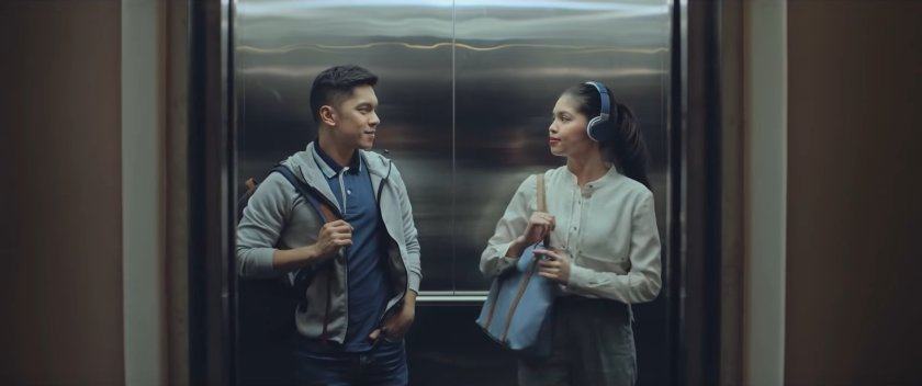 Carlo Aquino and Maine Mendoza as Gali and Mara in 'Isa Pa, With Feelings' (2019), standing inside an elevator, looking at each other and politely smiling.