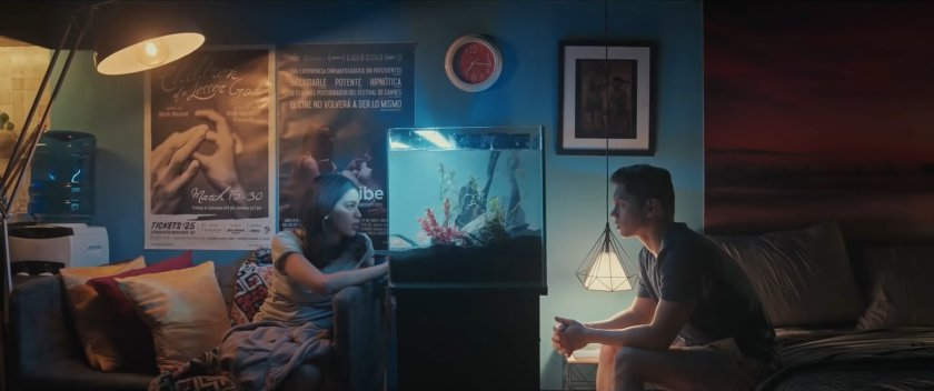 Maine Mendoza and Carlo Aquino as Mara and Gali in 'Isa Pa, With Feelings' (2019), inside Gali's condo unit, with colorful lighting, the two characters looking at each other but with an aquarium between them.